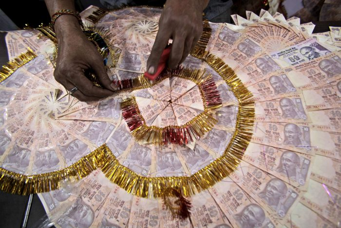 In this Nov. 11, 2016 file photo, a shopkeeper prepares a garland with Indian 10 Rupees denomination notes, used particularly to garland grooms on their wedding day, in Jammu, India.