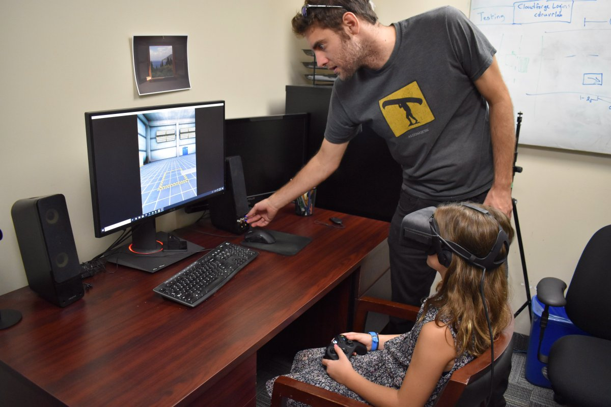 Andrew Vierich, a software developer at the University of Guelph, looks on as Ruby Corbett learns how to safely cross streets using a virtual reality program Vierich helped design in this undated handout photo.