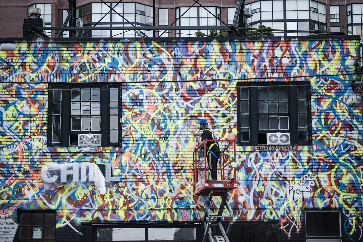 Anthony Ricciardi spray paints the eastern facade of a commercial establishment on Bathurst Street in Toronto, on Monday, July 30, 2018.