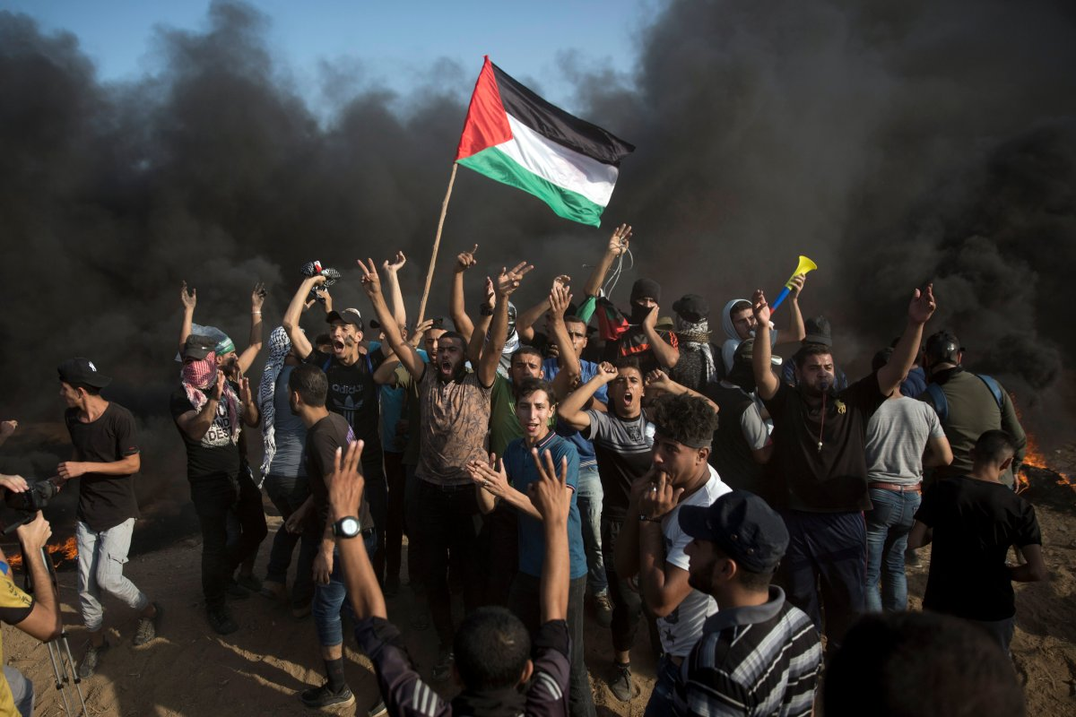 Palestinians chant slogans in front of black smoke rising from burning tires during a protest at the Gaza Strip's border with Israel, Friday, Sept. 28, 2018.