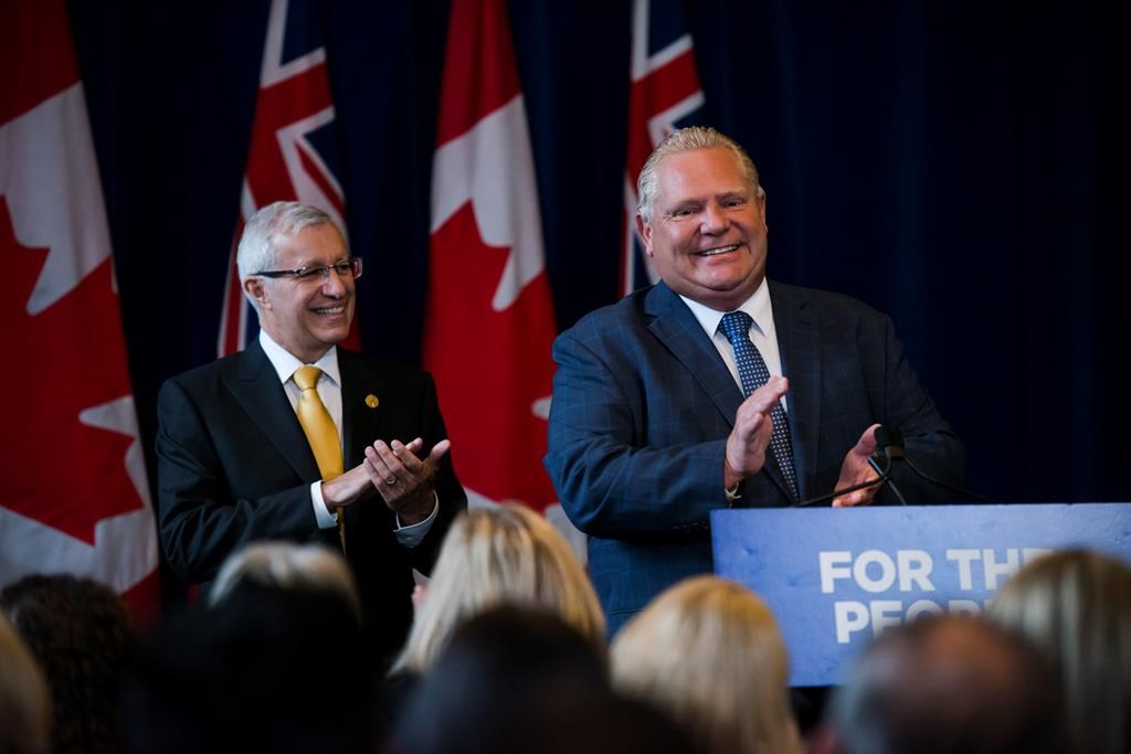 Finance Minister Vic Fedeli applauds alongside Premier Doug Ford after speaking to members of his caucus in Toronto on Monday, Sept. 24, 2018.