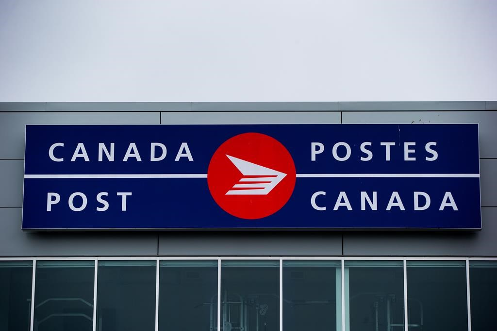The Canada Post logo is seen on the outside the company's Pacific Processing Centre, in Richmond, B.C., on Thursday June 1, 2017. An arbitrator has released a ruling in a long-standing pay equity dispute at Canada Post that gives rural carriers a hefty pay increase. THE CANADIAN PRESS/Darryl Dyck.