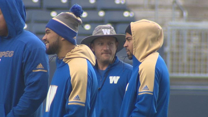 Winnipeg Blue Bombers receiver Nic Demski and running back Andrew Harris watch practice at Investors Group Field.