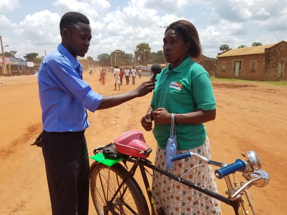 Alex Misogo of Anisa radio interviews a woman who rides her bicycle daily to and from work as part of JHR CRN field training in Yambio, South Sudan.