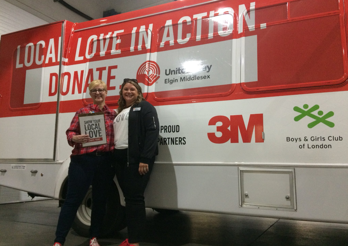 Kelly Ziegner, CEO of United Way of Elgin and Middlesex and Kyla Woodcock, the organization's 2018 campaign chair and first Chief ChangeMaker stand by the Local Love in Action bus at the 3M Harvest Lunch in London, Ont. on Sept. 20, 2018.