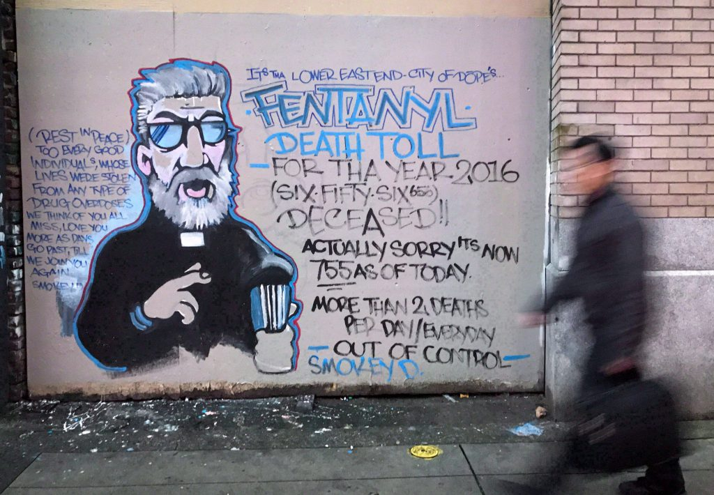 A man walks past a mural by street artist Smokey D. painted as a response to the fentanyl and opioid overdose crisis, in the Downtown Eastside of Vancouver, B.C., on Thursday, December 22, 2016.