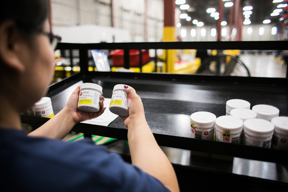A worker sorts jars of cannabis at the Ontario Cannabis Stores' warehouse in this handout image.