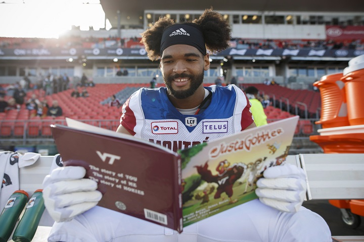 Montreal Alouettes defensive tackle Woody Baron (97) poses with his children's book on the sidelines in Toronto on Saturday, Oct. 20, 2018.