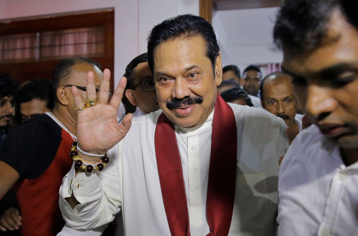 Newly appointed Sri Lankan Prime Minister Mahinda Rajapaksa, center, leaves a Buddhist temple after meeting his supporters in Colombo, Sri Lanka, Friday, Oct. 26, 2018.