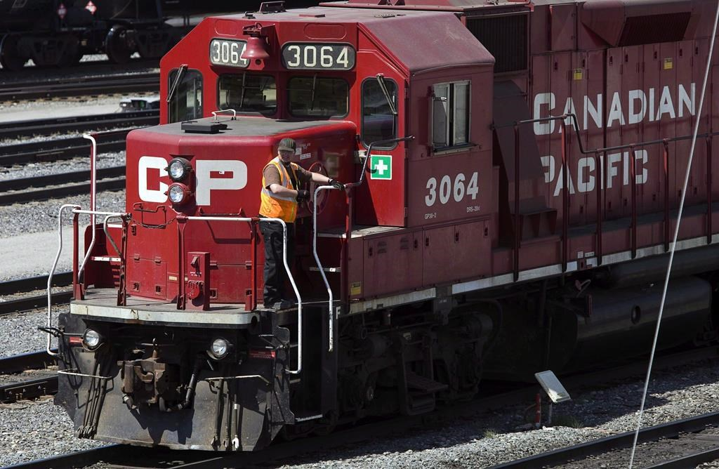File: A Canadian Pacific Railway employee walks along the side of a locomotive in a marshalling yard in Calgary, Wednesday, May 16, 2012.