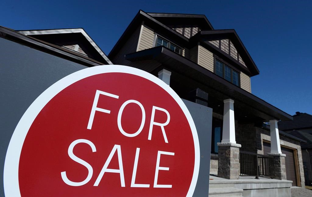 """A sign advertises a new home for sale in Carleton Place, Ont., on March 17, 2015. Despite an easing in prices, the Canadian housing market remains """"highly vulnerable,"""" according to the Canadian Mortgage and Housing Corporation. THE CANADIAN PRESS/Sean Kilpatrick."""