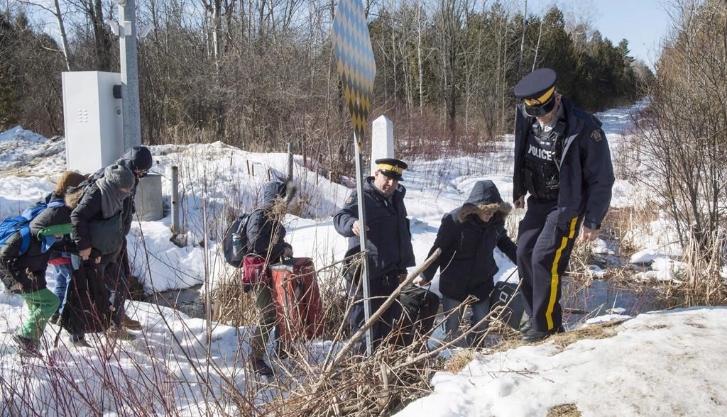 RCMP officers help a family of asylum claimants as they cross the border into Canada from the United States, Monday, February 20, 2017 near Hemmingford, Que. THE CANADIAN PRESS/Paul Chiasson.
