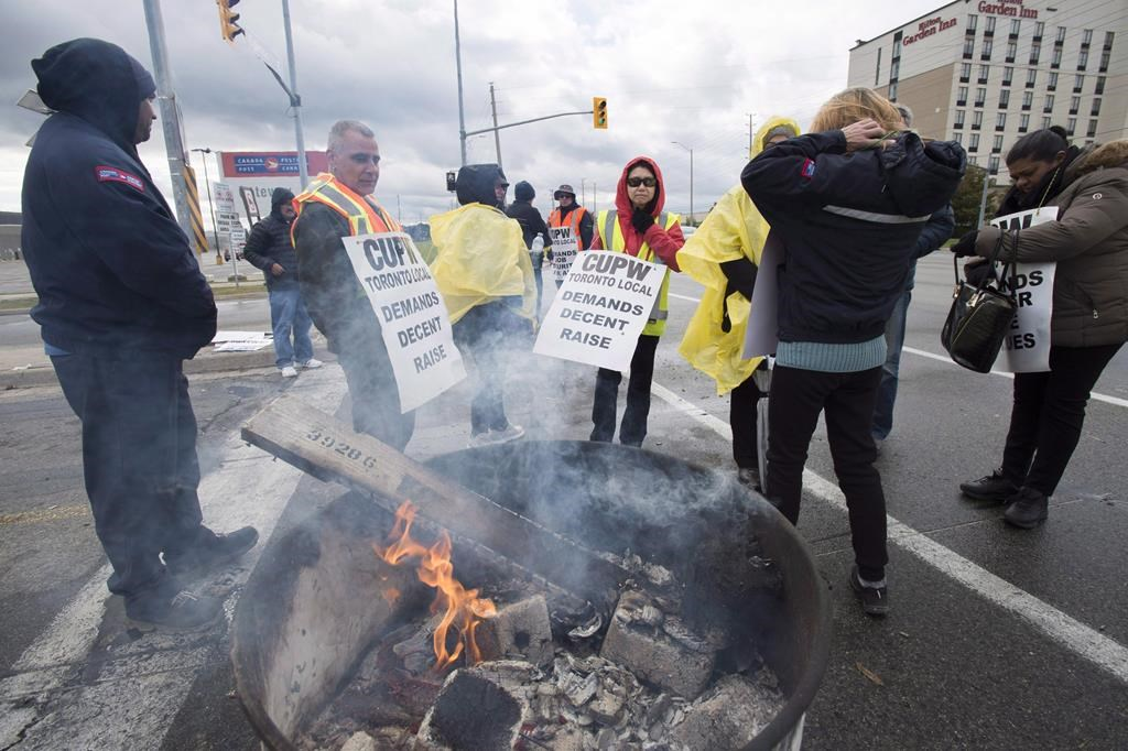 Striking Canada Post workers walk the picket line in Mississauga, Ontario on Tuesday, October 23, 2018.