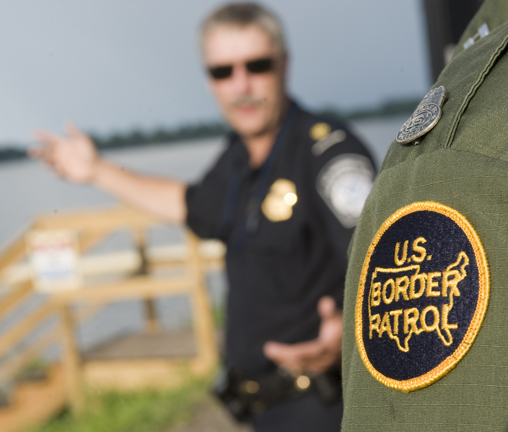 Supervisor Dan Moore of the Customs and Border Patrol agency speaks with Supervisor Richard Labounty of the US Border Patrol at a dock facility on Lake Champlain.