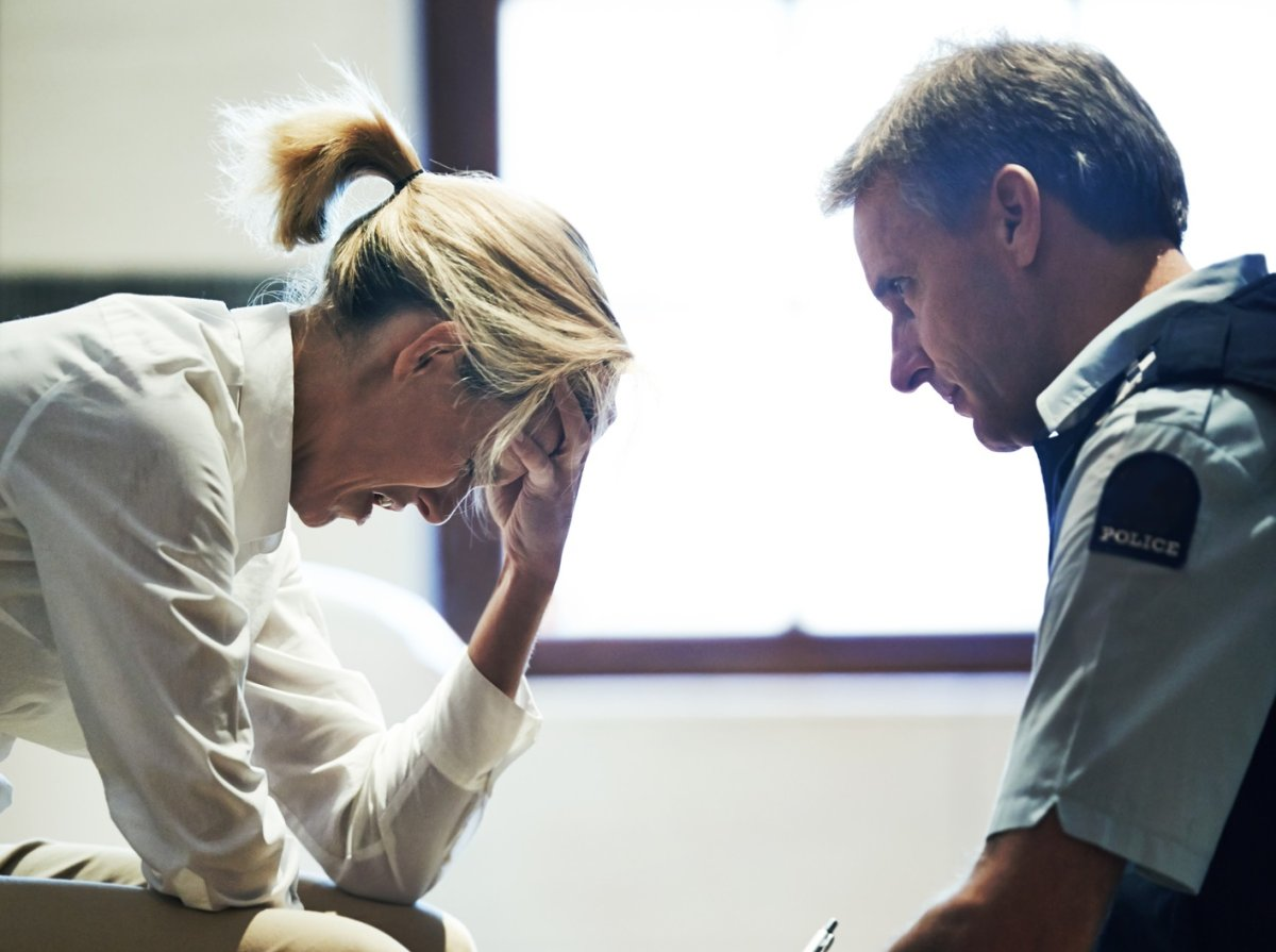 Shot of a grief stricken woman giving her statement to a police officer at a crime scene .