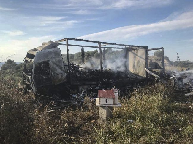 A burn-out truck on a field behind a small chapel, next to a motorway, following a collision near Greece's northern town of Kavala, Oct. 13, 2018.