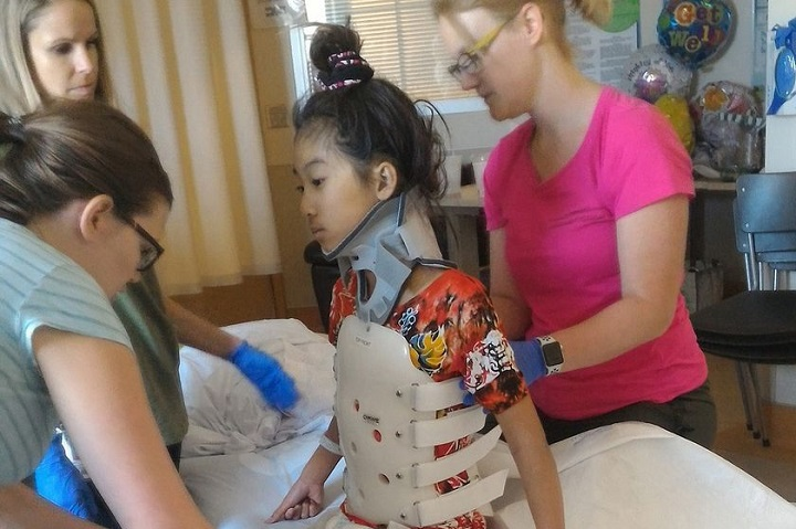 Hailey Cheng wears a stiff body brace in therapy to protect her spine at the Glenrose Rehabilitation Centre in Edmonton.