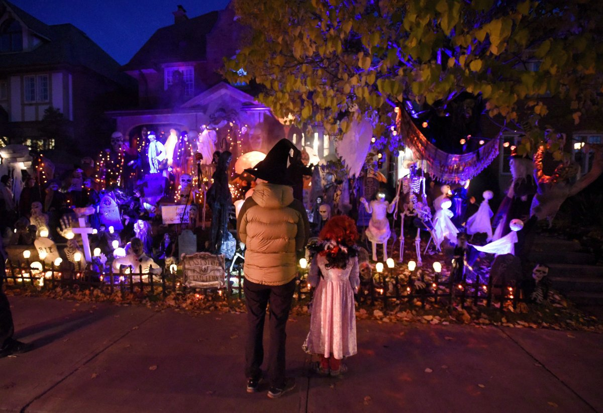 People go trick-or-treating at a decorated home in the Glebe neighbourhood in Ottawa on Halloween on October 31, 2016.
