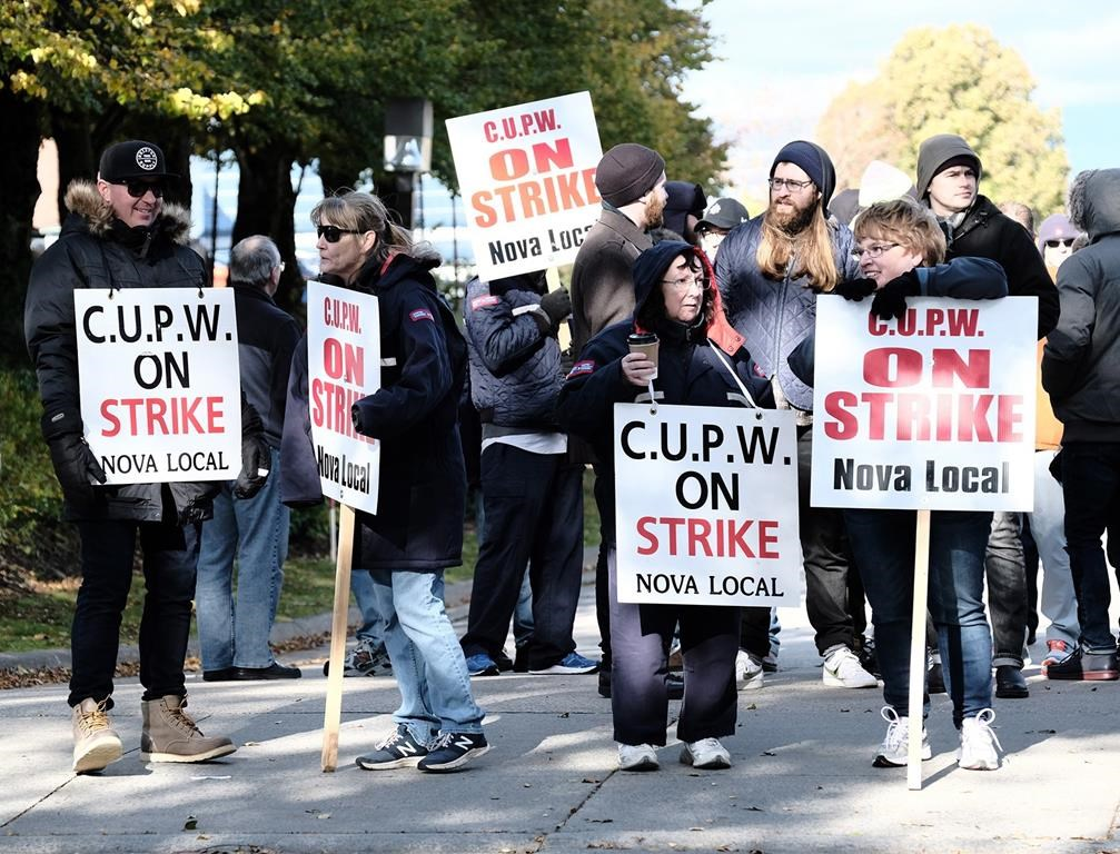 Canadian Union of Postal Workers (CUPW) members stand on picket line along Almon St., in front of the Canada Post regional sorting headquarters in Halifax on Monday, Oct.22, 2018 after a call for a series of rotating 24-hour strikes. THE CANADIAN PRESS/Ted Pritchard.