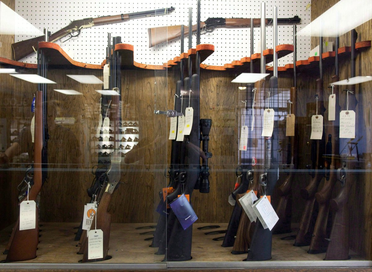 Hunting rifles are seen on display in a glass case at a gun and rifle store.