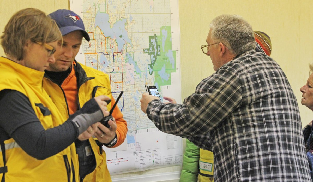 Little Divide Search and Rescue coordinator Natasha Downes and organization member Brad Seminiuk check radio contact with other searchers already in the area as community members check the  map for search areas during Saturday morning's staging of a ground search for Rosanna Giacobbo. Photo taken near Lac La Biche, Alta. on Saturday, October 13, 2018.