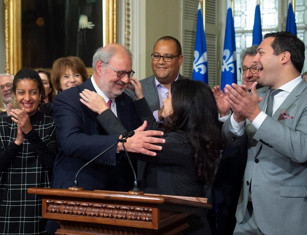 Interim Quebec Liberal opposition leader Pierre Arcand, centre left, is congratulated by Liberal caucus president Filomena Rotiroti, centre right, while caucus members applaud, on Friday, Oct. 5, 2018 at the legislature in Quebec City.