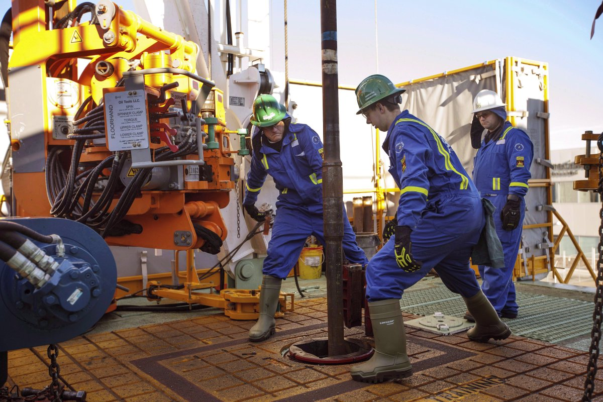 Trainees Dan Brook and Bradley Williams are directed by instructor Clint Dyck while training to lay down drill pipe on a rig floor, at Precision Drilling in Nisku, Alta., on January 20, 2016.