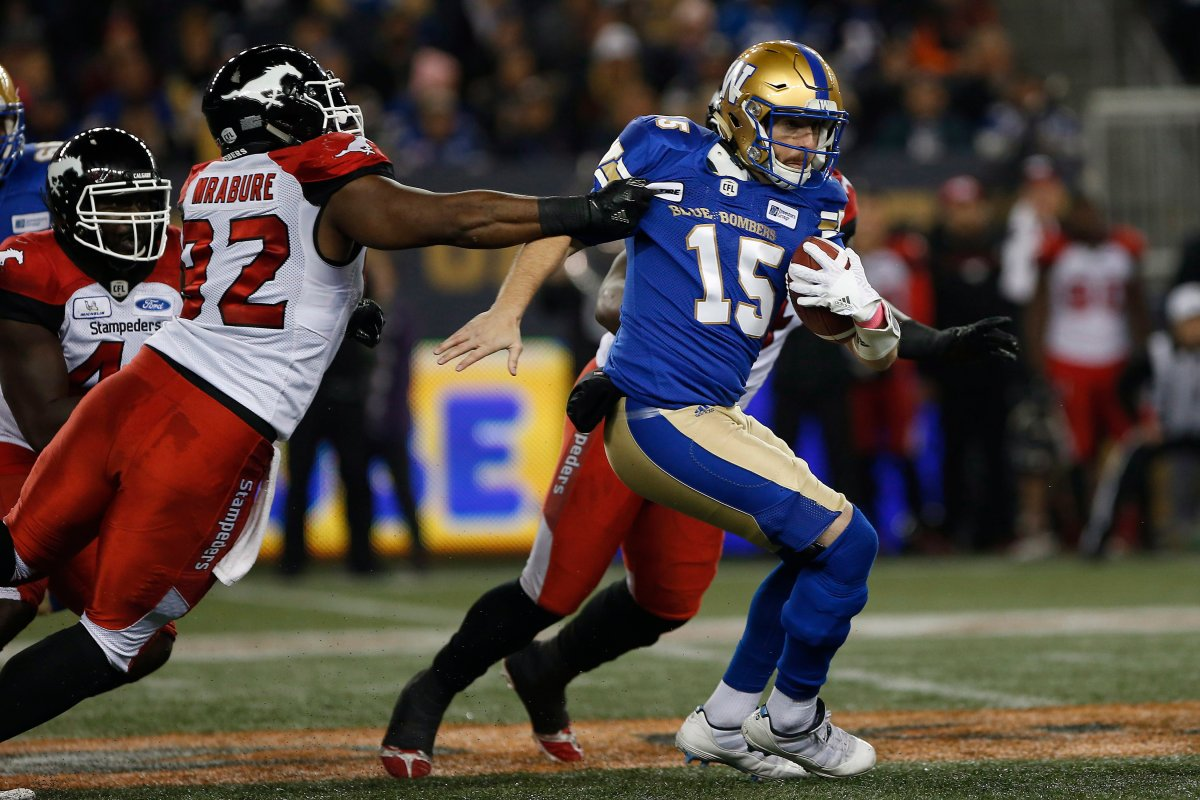 Winnipeg Blue Bombers quarterback Matt Nichols (15) attempts to get out of the grasp of Calgary Stampeders' Ese Mrabure (92) during the first half of CFL action in Winnipeg, Friday, Oct. 26, 2018.