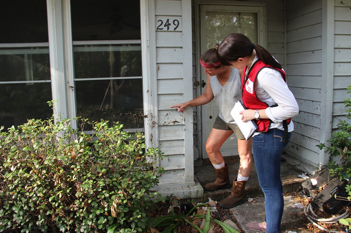 Canadian Red Cross member Stephanie Murphy with Meg, a woman in Wilmington, NC showing how high the water reached in her house when it flooded.