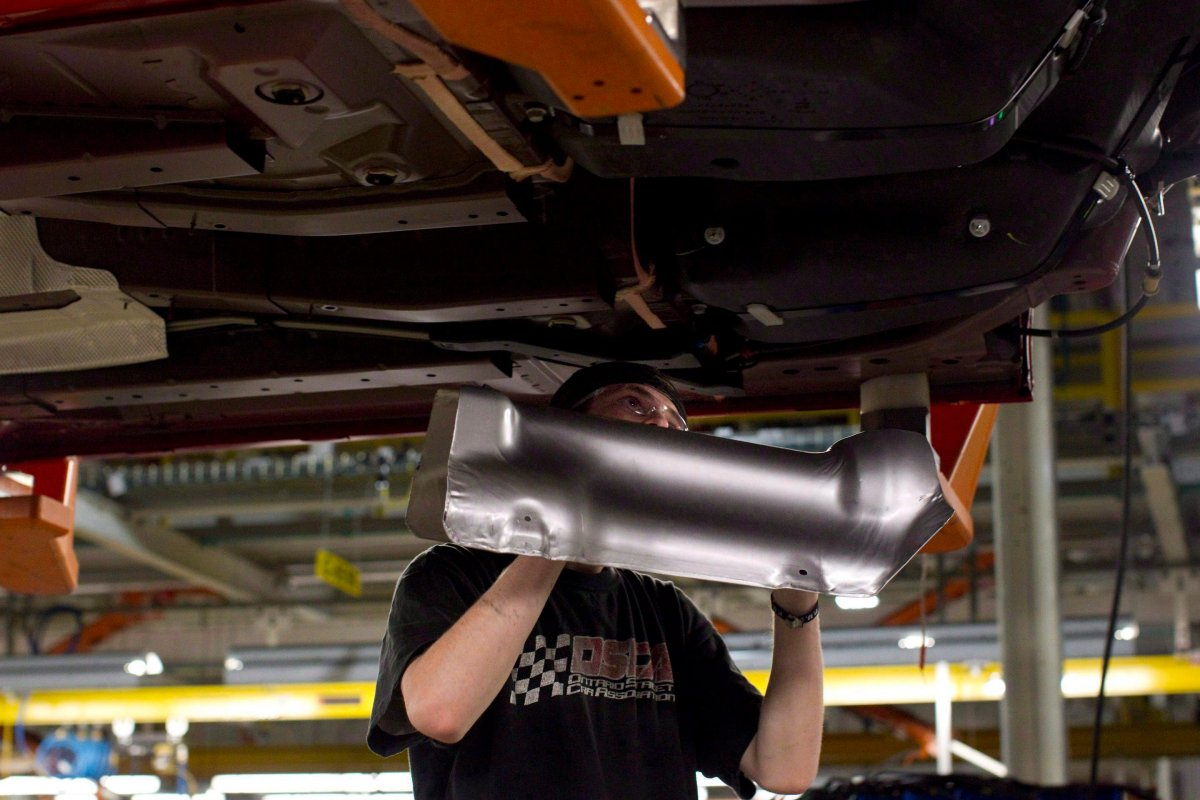 An assembly line worker at the General Motors Assembly plant in Oshawa works on a car on Friday December 16, 2011. General Motors and the Canadian auto workers union Unifor have reached a tentative contract agreement, averting a strike that was threatened for midnight Monday.
