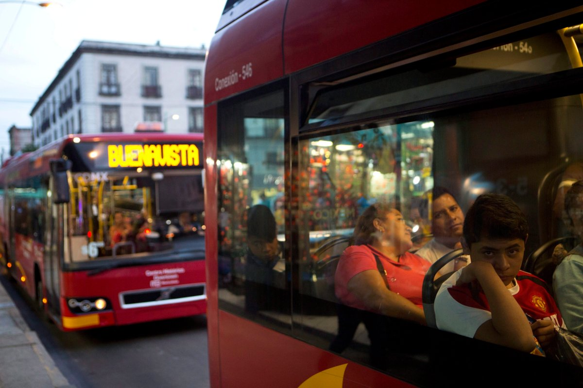 """Commuters ride a """"Metrobus"""" rapid transit bus as night falls in Mexico City, Friday, Dec. 2, 2016."""