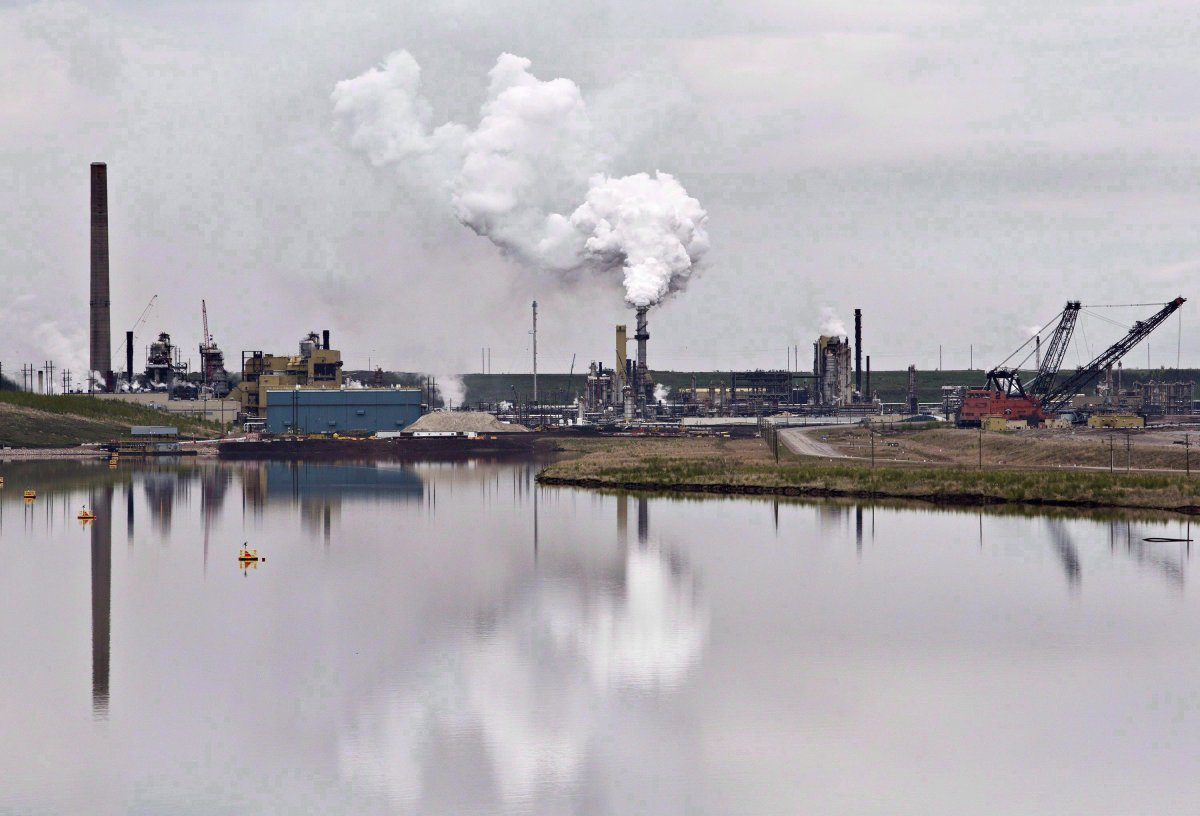 The Syncrude oil sands extraction facility is reflected in a tailings pond near the city of Fort McMurray, Alta. on Sunday, June 1, 2014. The Alberta Energy Regulator says it doesn't agree with a presentation given by a senior executive earlier this year that pegged the cost of cleaning up after the oil and gas industry at $260 billion. THE CANADIAN PRESS/Jason Franson.