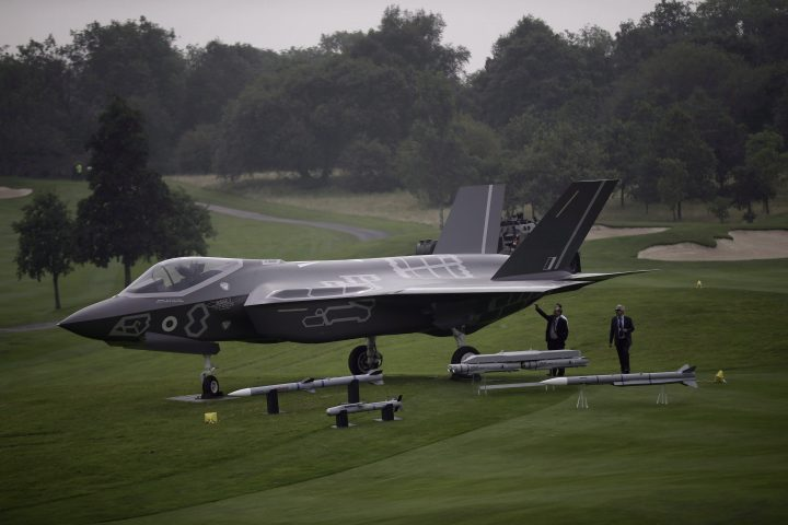 Men look at a demonstration F35 jet standing on display beside a golf course prior to a NATO summit at the Celtic Manor Resort in Newport, Wales, Wednesday, Sept. 3, 2014.