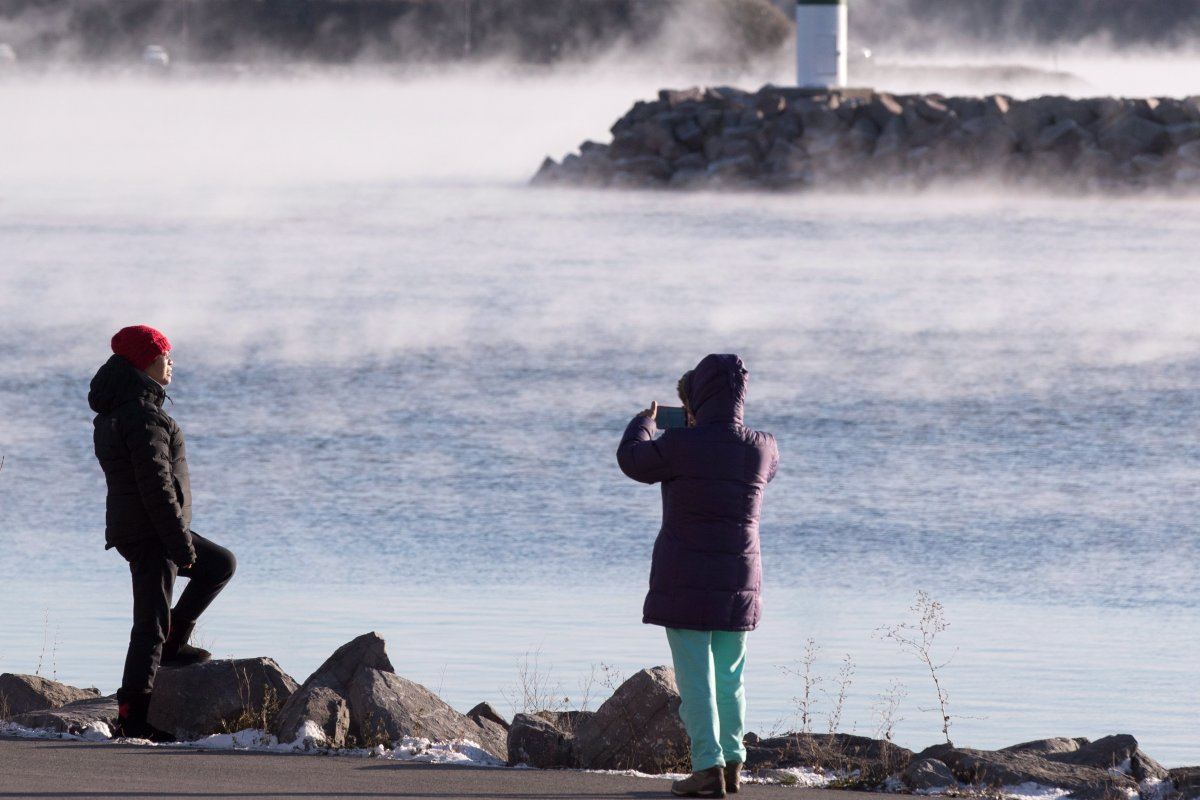 People take picture as mist rises from Lake Ontario during a winter cold snap in the area in Kingston, Ont. on Thursday, Nov. 22, 2018.