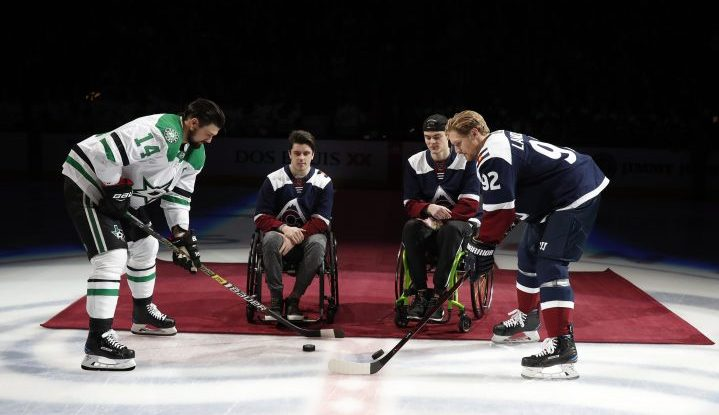 At left, Dallas Stars left wing Jamie Benn takes part in a ceremonial puck drop with Colorado Avalanche left wing Gabriel Landeskog, right, by two players from the Humboldt Broncos, Ryan Straschnitzki, second from left, and Jacob Wassermann, to open an NHL hockey game Saturday, Nov. 24, in Denver.