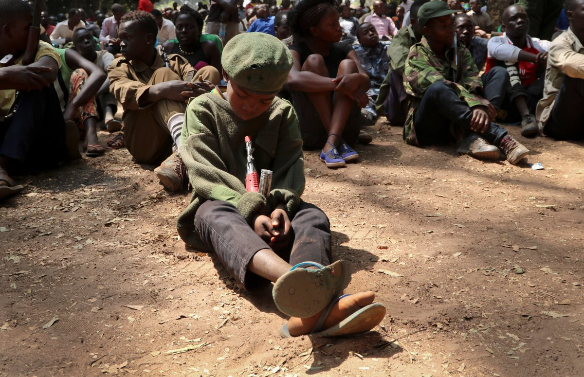 """A young child soldier sits on the ground at a release ceremony, where he and others laid down their weapons and traded in their uniforms to return to """"normal life"""", in Yambio, South Sudan, Feb. 7, 2018."""