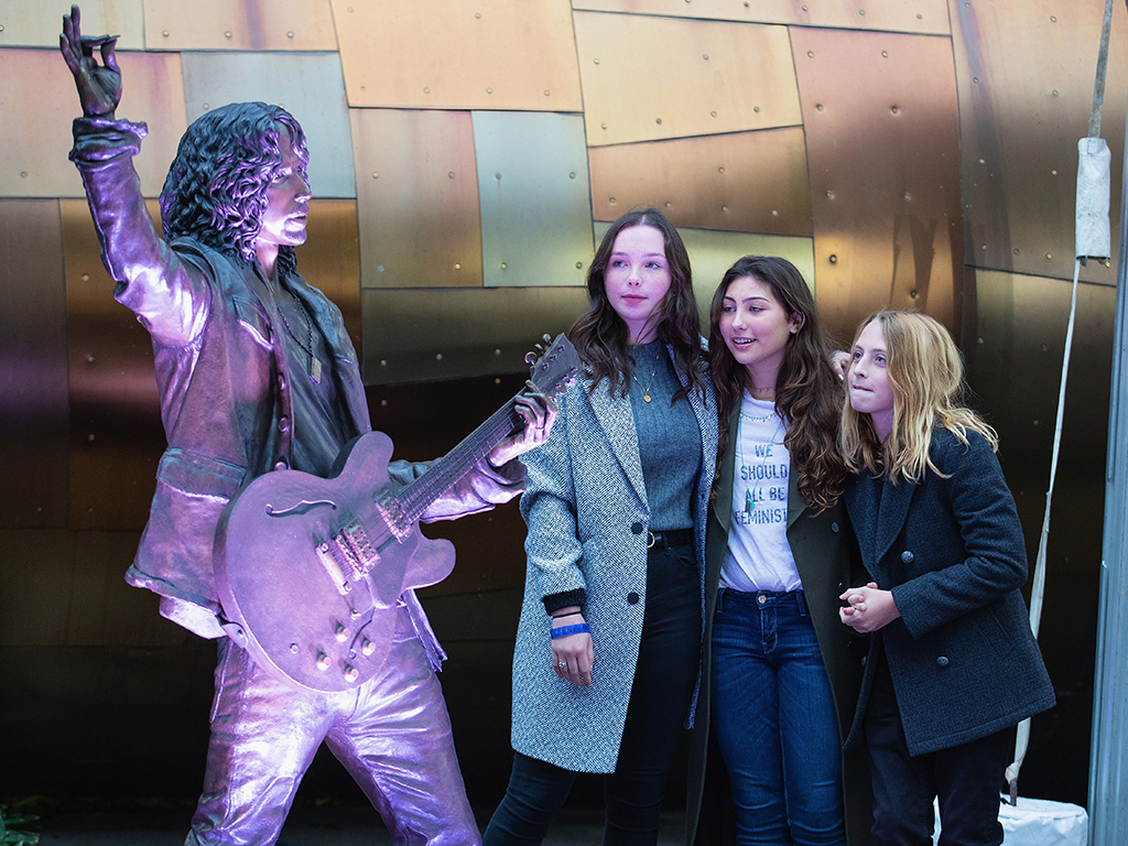 (L-R) Lily Cornell, Toni Cornell and Christopher Cornell unveil a life-size statue of their father, Chris Cornell during the public unveiling ceremony at MoPop on Oct. 7, 2018 in Seattle, Wash.