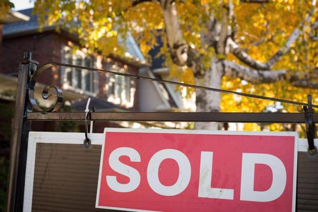 A real estate sold sign hangs in front of a home.