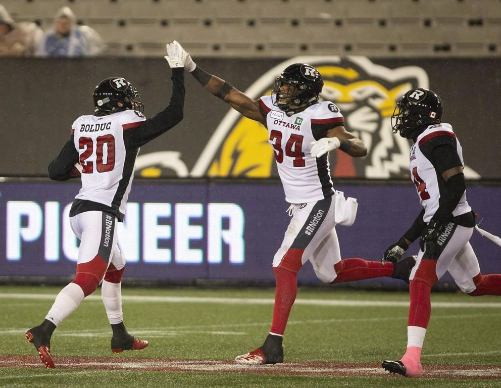 Ottawa Redblacks Kyries Hebert (34) celebrates with teammate Jean-Philippe Bolduc (20) after making an interception during second half CFL Football game action against the Hamilton Tiger-Cats in Hamilton, Ont. on Saturday, October 27, 2018. The Ottawa Redblacks will be without a number of its starters Friday night as they wrap up the regular season against the Toronto Argonauts, but the mindset remains the same.