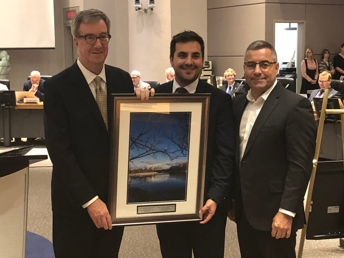 Coun. Michael Qaqish (centre) accepts a photo of the Chapman Mills Conservation Area as a farewell gift from Mayor Jim Watson and city manager Steve Kanellakos at a ceremony before council on Wednesday.