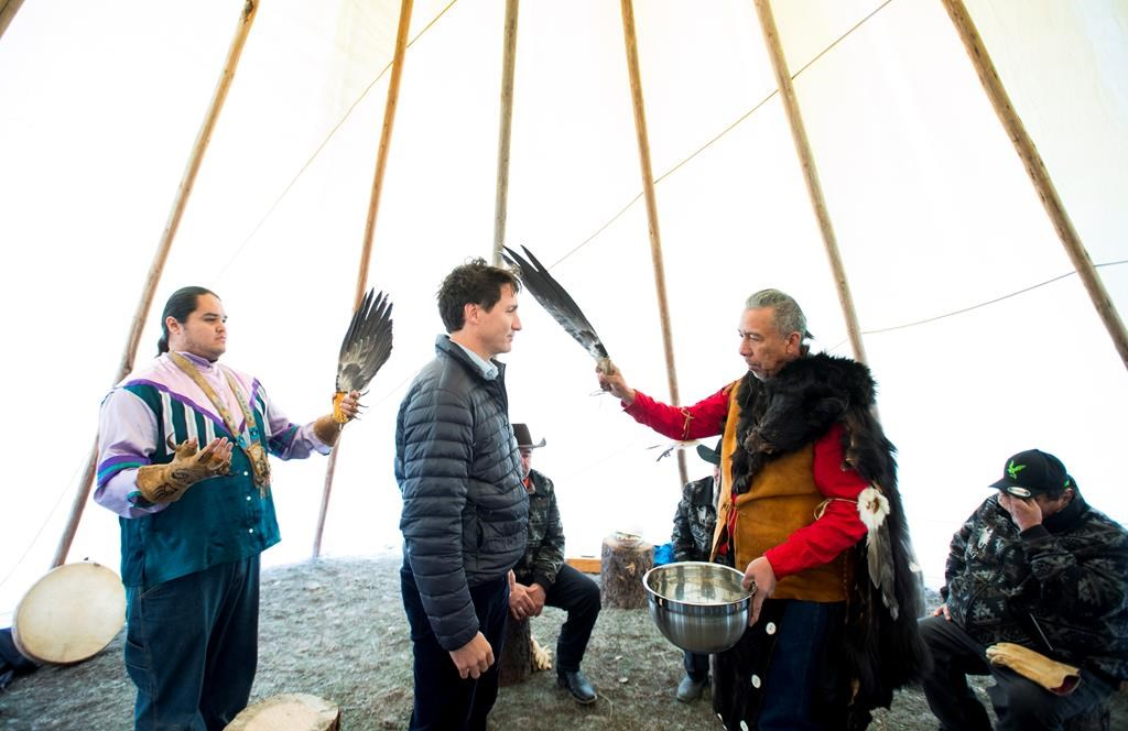 Prime Minister Justin Trudeau receives a water cleansing by spiritual leader Cecil Grinder along with Chiefs of the Tsilhqot'in National Government near Chilko Lake, B.C., Friday, Nov. 2, 2018.