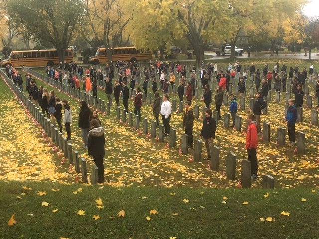 Students from Aldershot School place poppies on the graves of Canadian soldiers as part of the No Stone Left Alone initiative.