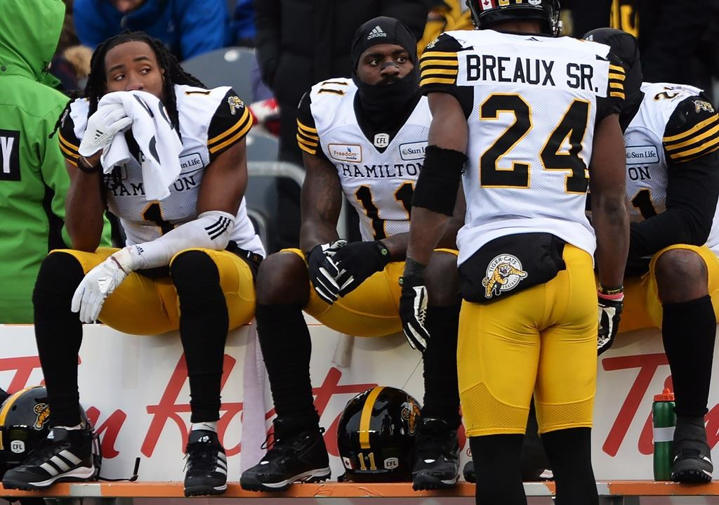 Hamilton Tiger-Cats players Don Unamba (1), Larry Dean (11) and Simoni Lawrence (21) sit on the bench as Delvin Breaux Sr. (24) looks on during second half CFL East Division Final action against the Ottawa Redblacks, in Ottawa on Sunday, Nov. 18, 2018.