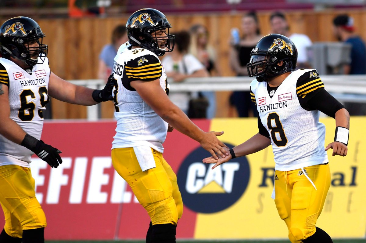 Hamilton Tiger-Cats quarterback Jeremiah Masoli (8) celebrates a conversion against the Ottawa Redblacks with Brandon Revenberg (57) and Landon Rice (60) during the first half of a pre-season CFL football game in Ottawa on Thursday, June 8, 2017.