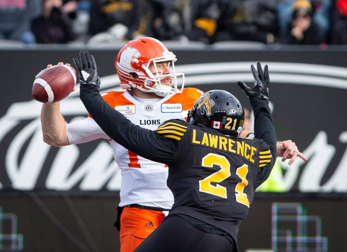 B.C. Lions quarterback Travis Lulay (14) is pressured by Hamilton Tiger-Cats linebacker Simoni Lawrence (21) during first half CFL Football division semifinal game action in Hamilton, Ont. on Sunday, November 11, 2018.