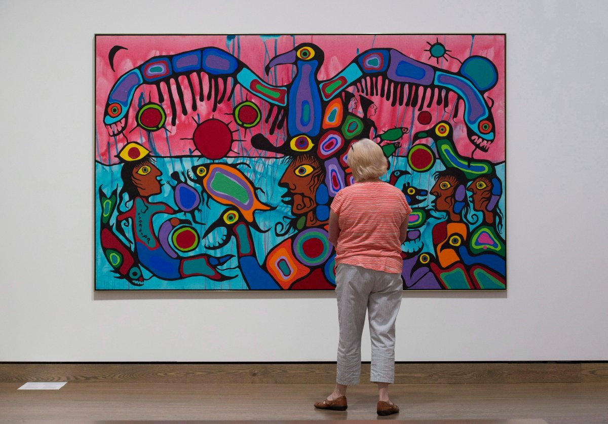 """A woman surveys the painting """"Copper Thunderbird"""" by Norval Moreisseau on display during a media tour of the National Gallery of Canada's Canadian and Indigenous Galleries featuring Canadian and Indigenous Art: From Time Immemorial to 1967 in Ottawa, Wednesday, June 7, 2017."""