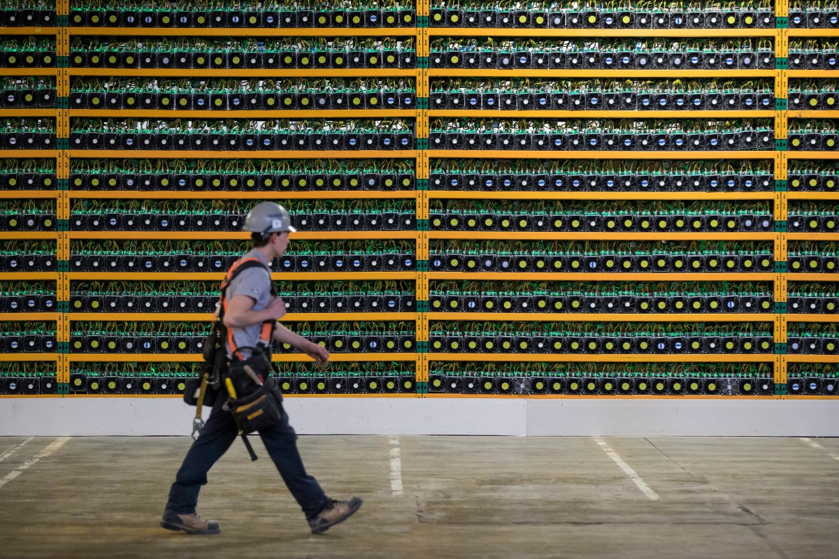 A construction worker walks past a wall of computers mining bitcoin at the Bitfarms company in Saint Hyacinthe, Quebec on Monday, March 19, 2018. THE CANADIAN PRESS IMAGES/Lars Hagberg.