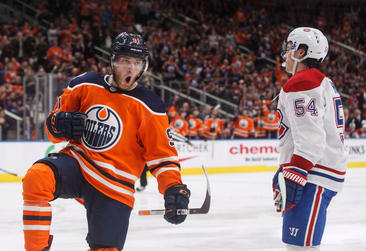 Montreal Canadiens' Charles Hudon (54) skates past as Edmonton Oilers' Drake Caggiula (91) celebrates a goal during second period NHL action in Edmonton, Alta., on Tuesday November 13, 2018. THE CANADIAN PRESS/Jason Franson.