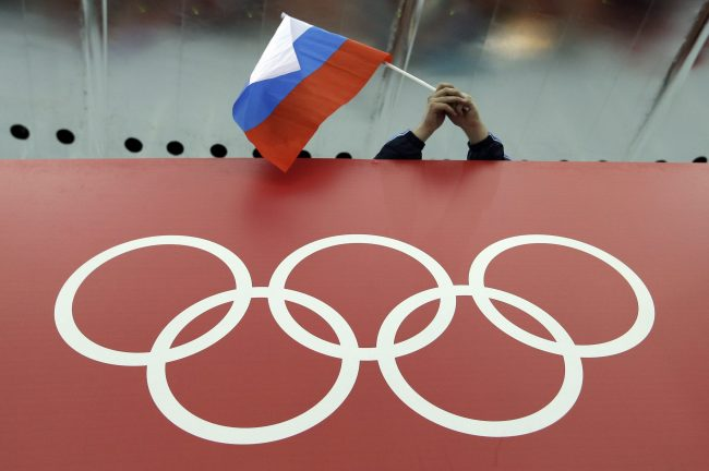 In this Feb. 18, 2014, file photo, a Russian skating fan holds the country's national flag over the Olympic rings at Adler Arena Skating Center during the 2014 Winter Olympics in Sochi, Russia.