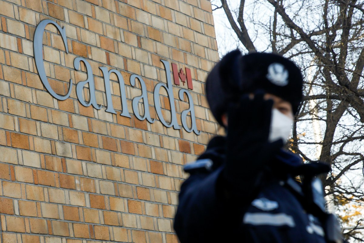 A police officer gestures at the photographer outside the embassy of Canada in Beijing, China, December 12, 2018. REUTERS/Thomas Peter.
